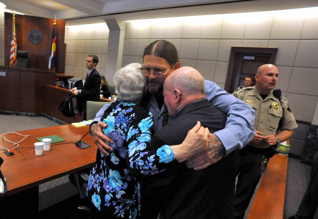 Robert Dewey embraces his parents after being exonerated from a murder conviction in Grand Junction Colo.