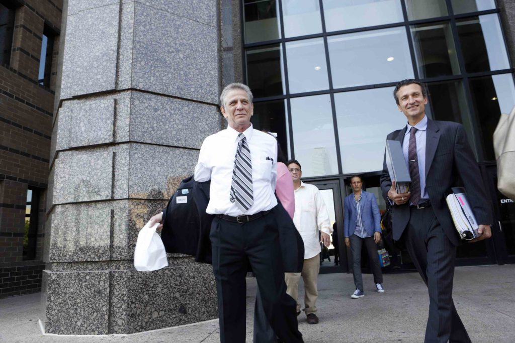 Steven Mark Chaney takes off his jacket while walking out of the Dallas courthouse this afternoon after a court reversed his 1987 murder conviction because of discredited bite mark testimony.Innocence Project Attorney M. Chris Fabricant is on the right. Photographed on Monday, October 12, 2015. (Photo copyright Lara Solt)